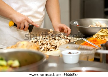 Chef cutting the mushrooms on a wooden board - stock photo