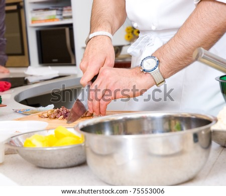 Chef cutting the olives on a wooden board - stock photo