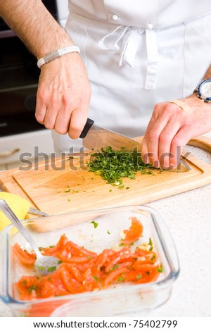 Chef cutting the parsley on a wooden board