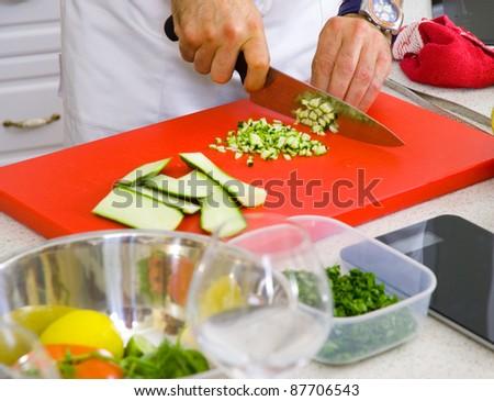 Chef cutting the zucchini on a board - stock photo