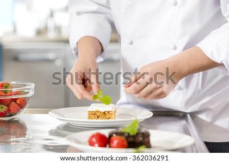 Chef decorate dessert cake with lemon leaf - stock photo
