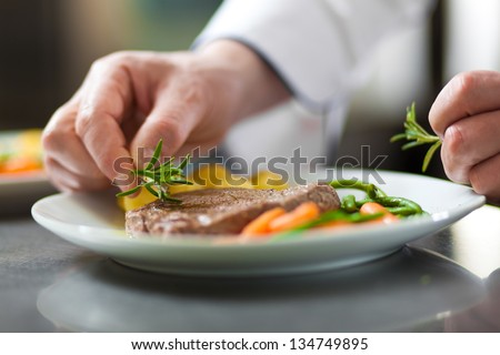 Chef decorating a dish in restaurant kitchen - stock photo