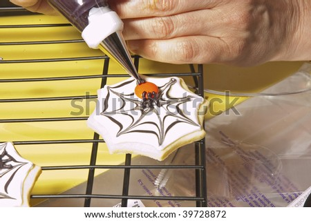Chef decorating cookies for halloween - stock photo