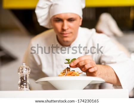 Chef dressed in white uniform decorating pasta salad - stock photo