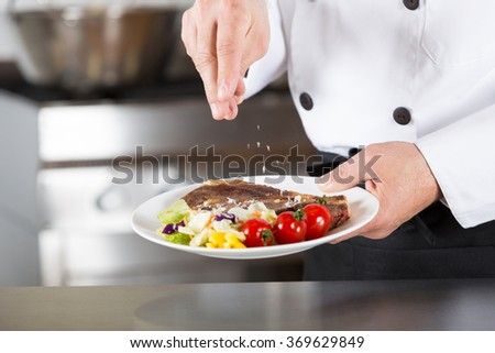 Chef finishing her plate and almost ready to serve at the table - stock photo