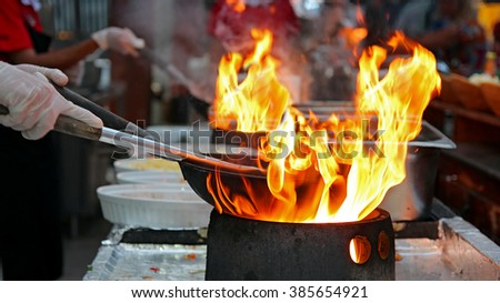 Chef Flambe Cooking. Professional chef in a commercial kitchen cooking flambe style.  Chef frying food in flaming pan on gas hob in outdoor kitchen. - stock photo