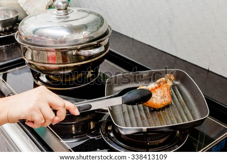 chef fried pork steak in a pan - stock photo