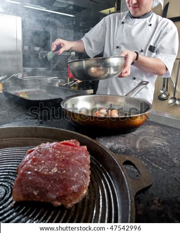 Chef frying different courses on stove - stock photo