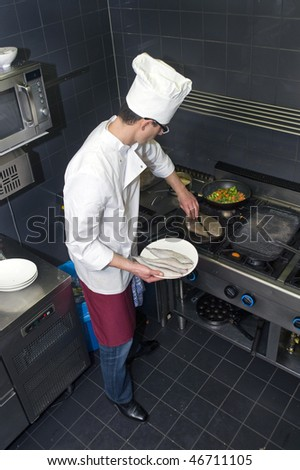 Chef frying dover sole in a professional restaurant kitchen - stock photo
