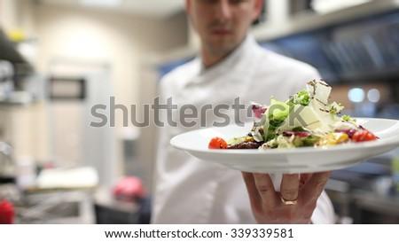 Chef garnishing salads in the kitchen garnishing their salads - stock photo