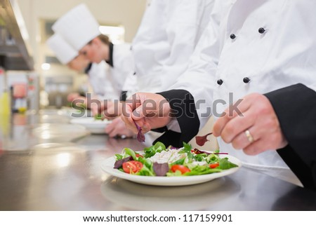 Chef garnishing salads in the kitchen with others garnishing their salads - stock photo