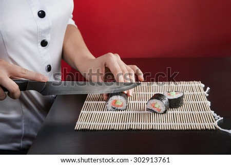 Chef girl in a white coat makes the sushi on a black table. close-up - stock photo
