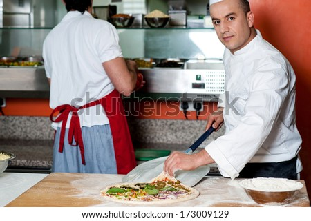 Chef giving last touches to vegetable pizza - stock photo