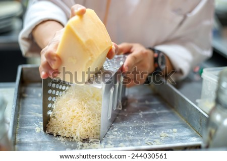 Chef grating cheese - stock photo