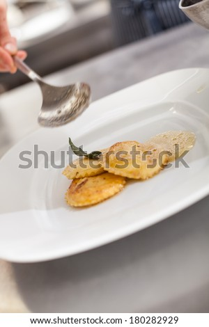 Chef grating truffle mushroom shavings onto homemade ravioli in a restaurant kitchen while preparing a dinner, close up view of the counter, plate and hands - stock photo