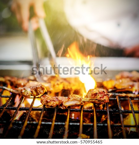 chef grilling lamb ribs on hot flame , barbecue cooking in evening and sunset