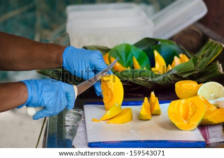 Chef hands slice Papaya fruit in outdoor kitchen on Pacific Island