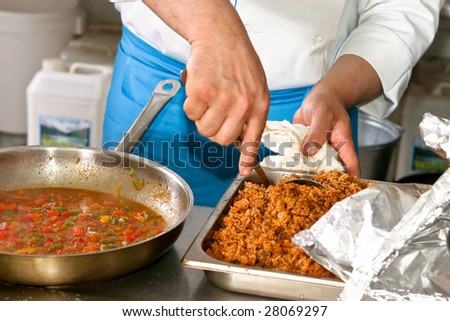 Chef hands with frying pan on professional kitchen - stock photo