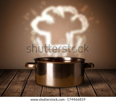 Chef hat coming out from cooking pot on wooden table - stock photo