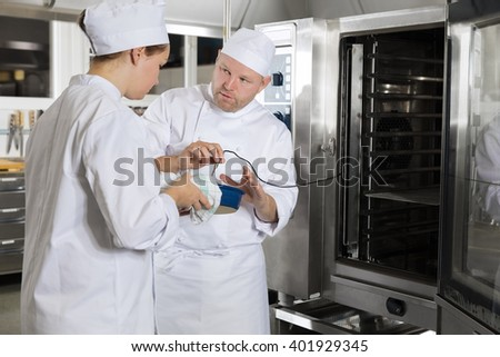 Chef helps student with cooking in a large kitchen - stock photo