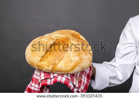 Chef holding a big rustic bread over gray background - stock photo