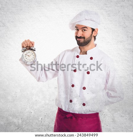 Chef holding a clock over textured background - stock photo