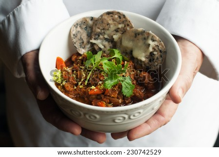 Chef holding bowl of chili with lime zest and cilantro garnish - stock photo