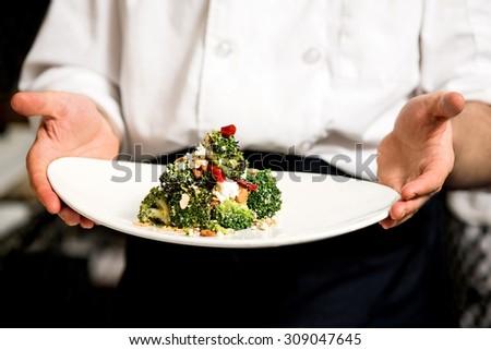 Chef holding broccoli salad, ready to serve - stock photo