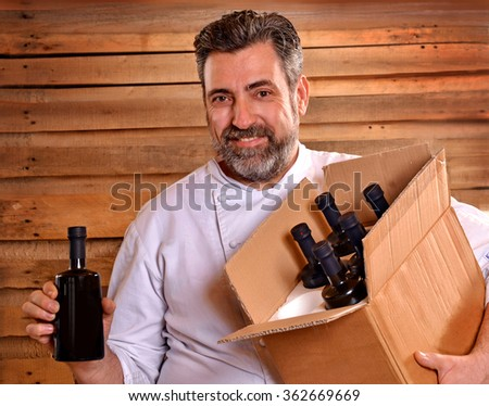 Chef holding extra virgin olive oil bottles box. - stock photo