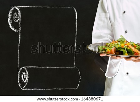 Chef holding health salad dish with chalk scroll on blackboard Background - stock photo
