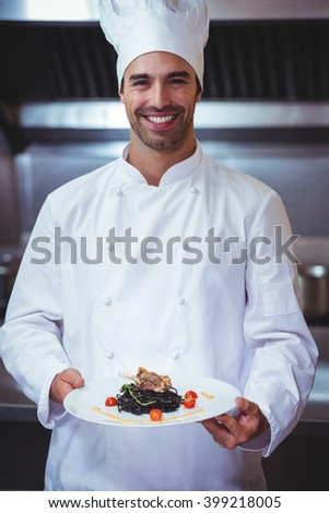 Chef holding his dish in commercial kitchen - stock photo