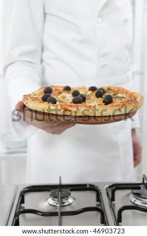 Chef holding pizza with olives