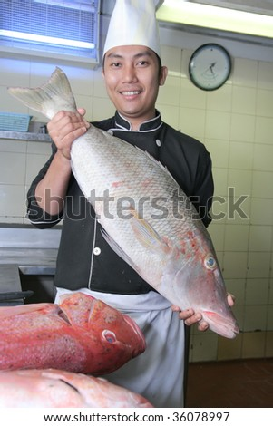 chef holding snapper fish at work - stock photo