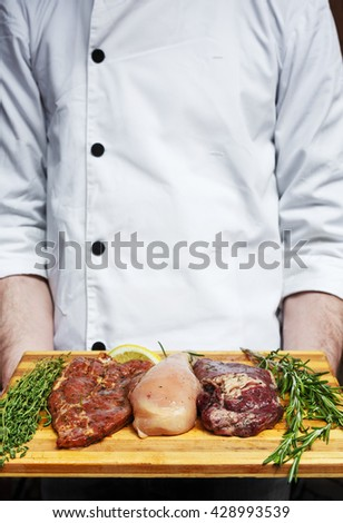 Chef holds fresh steaks ready for BBQ cooking - pork, beef and chicken. Raw meat on a cutting board with rosemary leaf. Raw pork meat on wood, closeup. Marinated in spices raw steak for barbecue. - stock photo