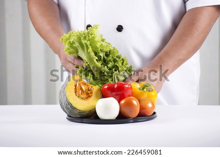 Chef holds tray of vegetable for prepared making salad.