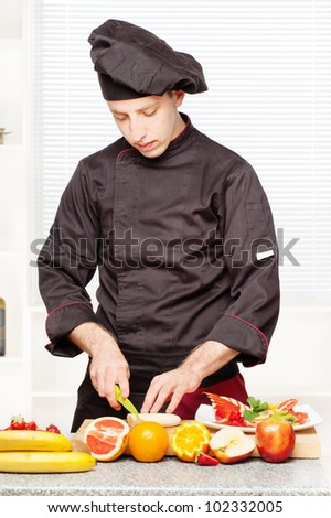 chef in black uniform cutting fruit on board in kitchen - stock photo