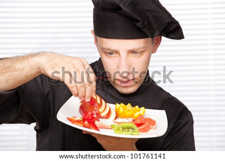 chef in black uniform decorating delicious fruit plate - stock photo