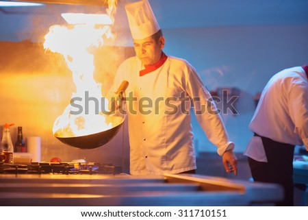 chef in hotel kitchen prepare vegetable  food with fire - stock photo