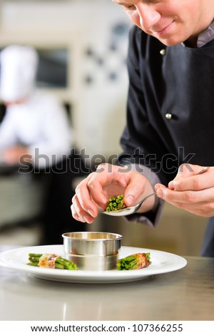 Chef in hotel or restaurant kitchen cooking, he is working on the sauce for the food as saucier - stock photo