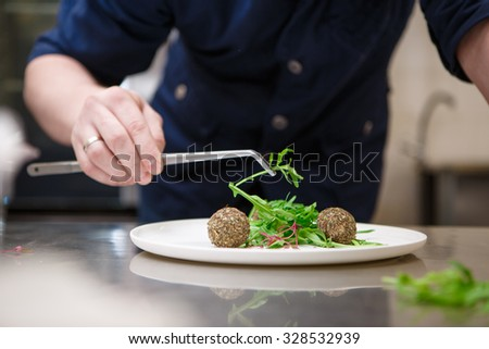 Chef in hotel or restaurant kitchen cooking, only hands - stock photo
