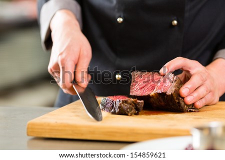 Chef in hotel or restaurant kitchen cooking, only hands, he is cutting meat or steak - stock photo