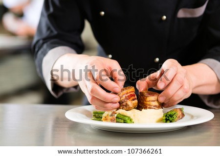 Chef in hotel or restaurant kitchen cooking, only hands to be seen, he is working on finishing a dish - stock photo