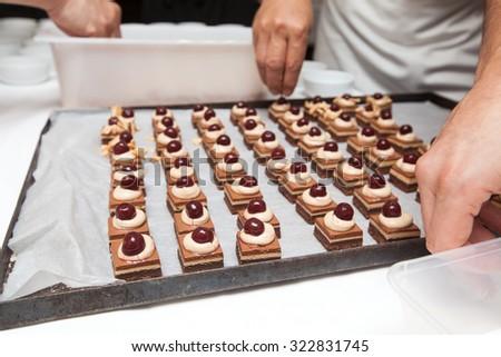 Chef in hotel or restaurant kitchen making dessert for dinner - stock photo