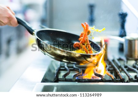 Chef in restaurant kitchen at stove with pan, doing flambe on food - stock photo