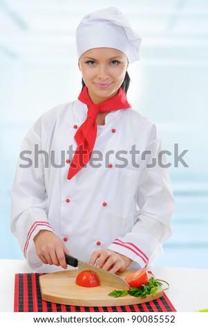 Chef in uniform cuts the tomato in the kitchen. - stock photo