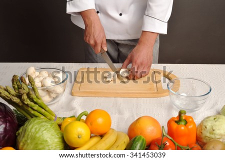 chef in uniform cutting fresh mushrooms in the kitchen - stock photo