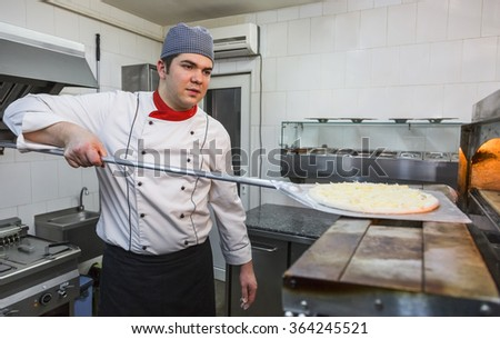 Chef introducing a pizza in a hot oven in a restaurant kitchen.