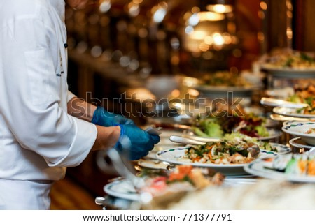 Chef arranging food on buffet table stock photo 771377791 shutterstock chef is arranging the food on buffet table watchthetrailerfo