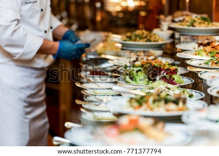 Chef arranging food on buffet table stock photo 771377794 shutterstock chef is arranging the food on buffet table watchthetrailerfo