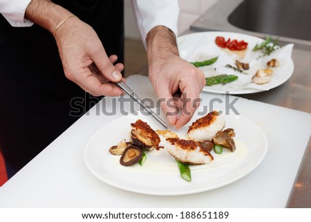 Chef is cooking a fish dish with vegetables and mushrooms - stock photo